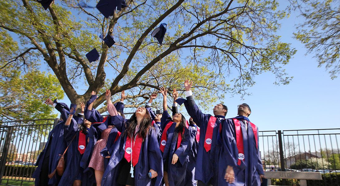Recent graduates throwing their caps in the air