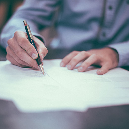 A person in a button up, long-sleeved shirt writing with a pen on a stack of papers.